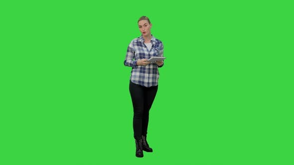 Cover Image for Young Woman Using Reading Presentation From a Tablet on a Green Screen, Chroma Key