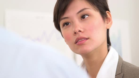 Thumbnail for Asian businesswoman listening to business partner