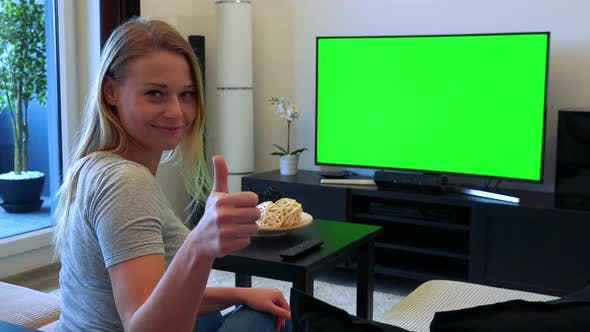 Thumbnail for Woman Sits on Couch in Living Room, Watches TV Green Screen and Agrees (Shows Thumb on Agreement)