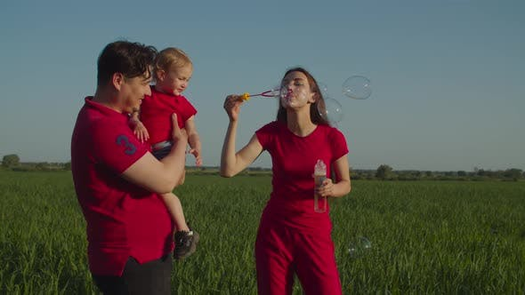 Thumbnail for Excited Family with Child Blowing Soap Bubbles