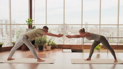 Couple Doing Forward Bends Practicing Yoga