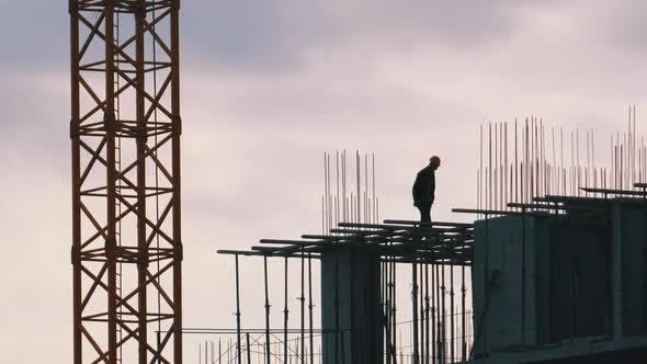 Thumbnail for Silhouette of a Builder on the Edge of a Skyscraper Under Construction. Workers at a Construction
