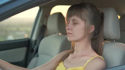 Young female driver resting behind the wheel of her car.