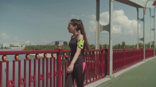 Thumbnail for Sporty Female Jogging and Doing Push Ups on Bridge