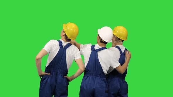 Thumbnail for Three Male Construction Workers in Hardhats Looking at the Work Site and Discussing It with Their