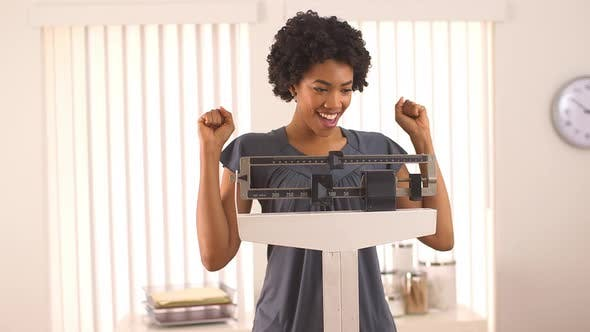 Thumbnail for Black woman excited about weight loss on scale