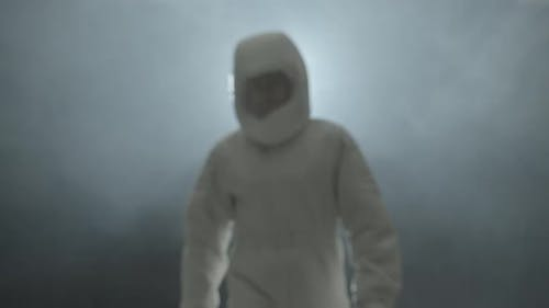 An Astronaut in a Spacesuit Walks in the Fog and Smiles