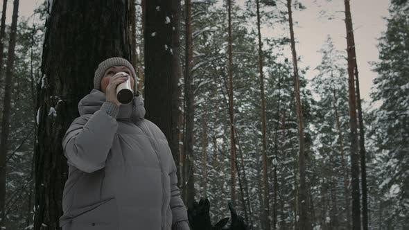 Frau ruht sich mit Tee im Thermosbecher im Wald aus