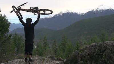 A mountain biker lifting bike over his head in celebration