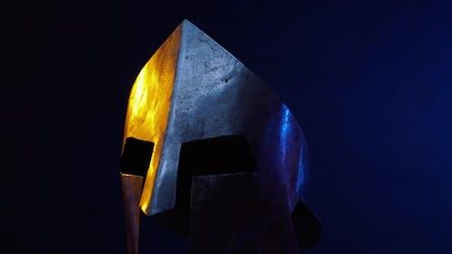 Средневековый металлический шлем, изолированный во тьме.