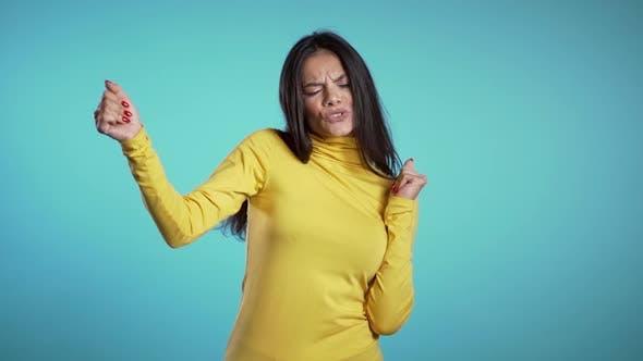 Thumbnail for Funny hispanic woman having fun, smiling, dancing in studio against blue background