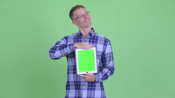 Thumbnail for Portrait of Happy Hipster Man Thinking While Showing Digital Tablet