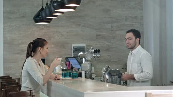 Thumbnail for Smiling Barista Talking To Female Client Finishing Her Drink