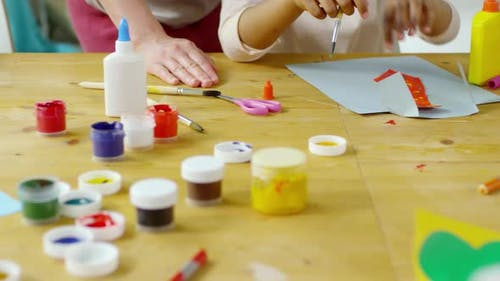 Close Up of Hands of Kids Painting and Making Paper Crafts in Art Class