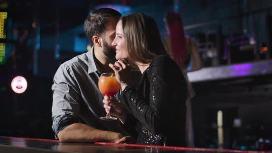 Young Attractive Caucasian Woman Drinking Cocktail and Talking with Handsome Middle Eastern Man