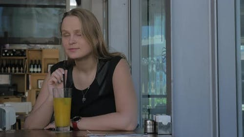 Young Wistful Woman Having Drink in Cafe