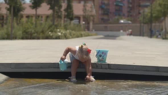 Thumbnail for Baby Girl Playing in Fountain on Hot Day