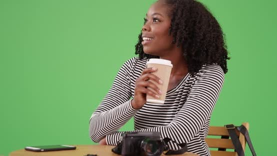 Thumbnail for Cute black woman sits at table holding coffee cup, looking around on greenscreen