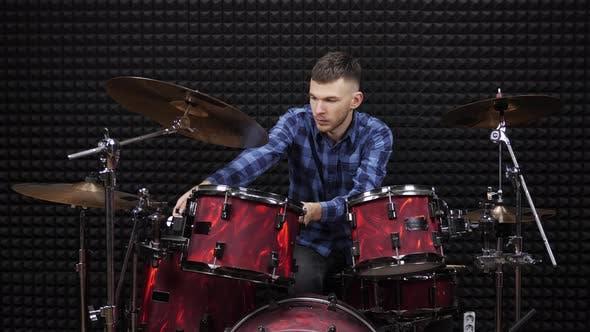 Drummer is tuning drum kit in professional rehearsal studio