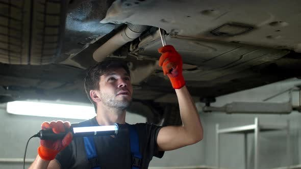 Mechanic with a Flashlight Repairs a Car
