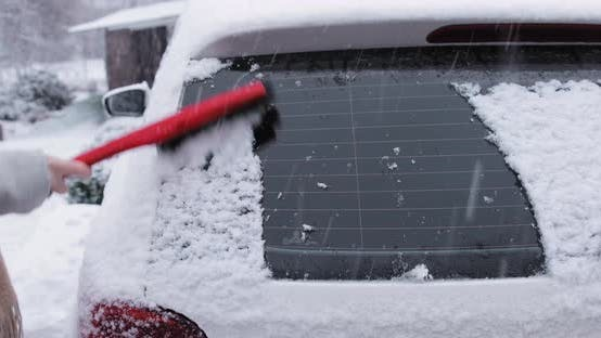 Thumbnail for Woman Cleaning Snow From Her Car Rear Window