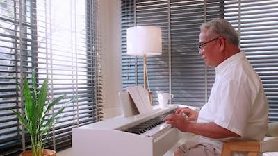 An elderly Asian man practicing playing the piano in the living room