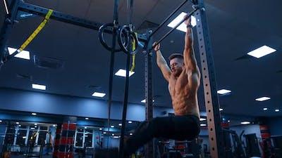 Bodybuilder exercising on horizontal bar. Shirtless man pulling up on horizontal bar in gym