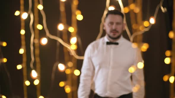 Cover Image for Confident Man Posing in Room with Fairy Lights