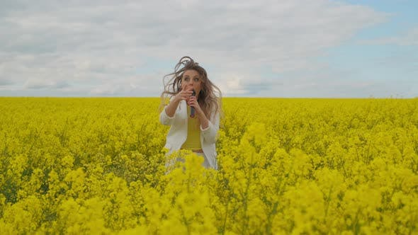 Thumbnail for Beautiful Girl Singer in a Yellow Field Dancing and Energizing Looking at the Camera