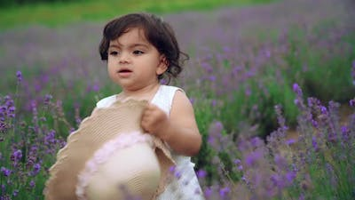 Baby Girl Carrying Straw Hat in Lavender Field