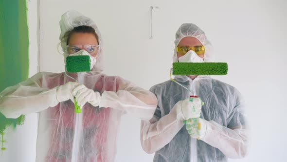 Couple in Workwear with Respirators Holds Rollers in Room