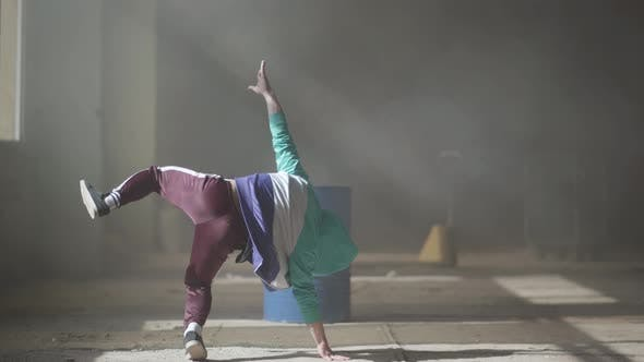 Thumbnail for Experienced Young Hip-hop Dancer Dancing Near the Barrel in an Abandoned Building in the Fog