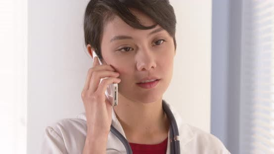 Thumbnail for Attractive Asian doctor talking on smartphone
