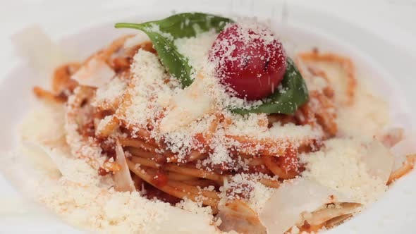 Thumbnail for Close-up Sprinkle Grated Tasty Cheese Parmesan To Fresh Appetizing Pasta Dish on Plate at Restaurant