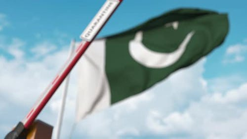 Barrier Gate with QUARANTINE Sign Being Closed Near Flag of Pakistan