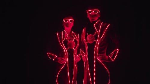 Darsteller in glühenden Kostümen stehen in glühenden roten Kostümen