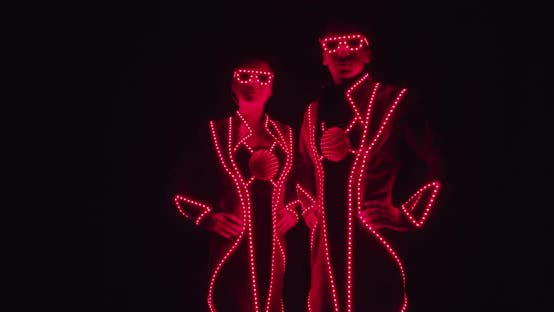 Thumbnail for Performers in Glowing Costumes Are Standing in Glowing Red Costumes