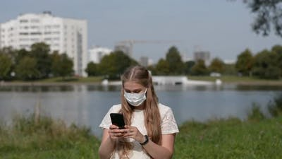 Woman Wear Face Mask and Use of Smart Phone at Outdoor