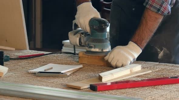 Cover Image for Man Working with Wooden Planck and Electric Planer Write in Notebook.