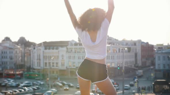 Attractive Mulatto Young Woman with Curly Hair Dancing on a Background of Modern Buildings - Sunset
