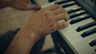 A Man Plays Music on a Keyboard Instrument