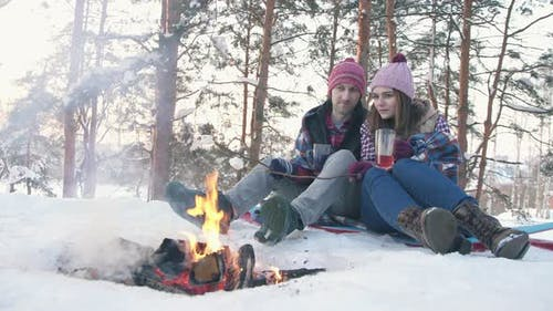 a Pair of Young People in Winter Clothes in a Snowcovered Forest Fry Marshmallows at the Stake