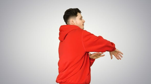 Handsome Young Man Dancing in Red Hoody on Gradient Background