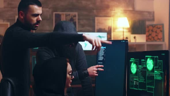 Team of Hackers Looking at Computer with Multiple Monitors