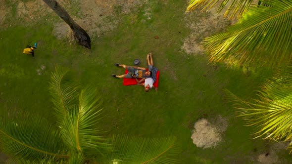 Cover Image for Happy Young Romantic Couple in Love Relaxing on Caribbean Beach Under Palms Tree