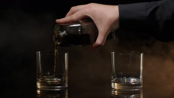 Barmann gießen Golden Whiskey Cognac Brandy Bourbon Rum aus der Flasche in Gläser auf dunklem Hintergrund