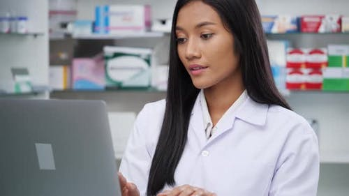 Pharmacist looking laptop computer for checking medication details in pharmacy drugstore