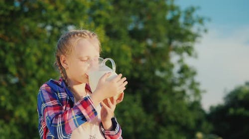 A Girl Drinks Milk From a Glass Jug in Her Garden. Healthy Organic Products Concept