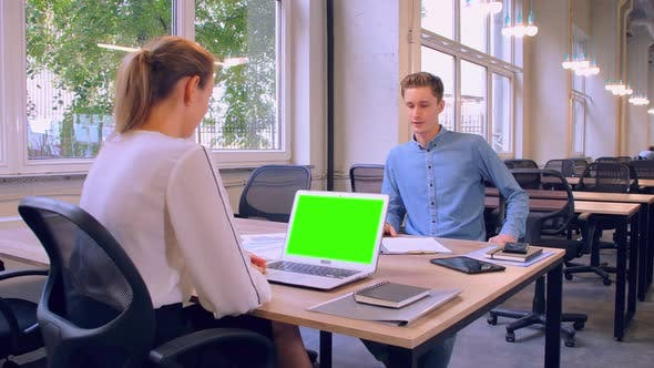 Thumbnail for Two Cheerful Colleagues Discussing in Modern Office