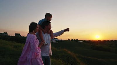 Happy Family Watching Sunset in Countryside